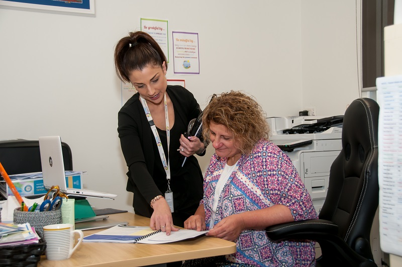 An authorised officer and an educator look at records in an office at an education and care service