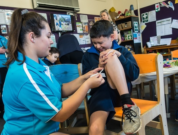 Educator putting a bandaid on a boy's knee at an out of school hours care service