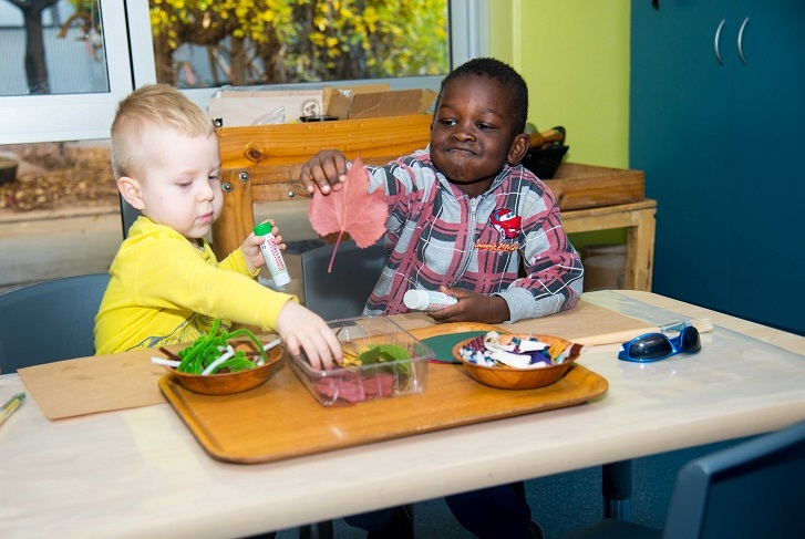 Two preschool-age boys doing an art project with leaves at a child-care centre