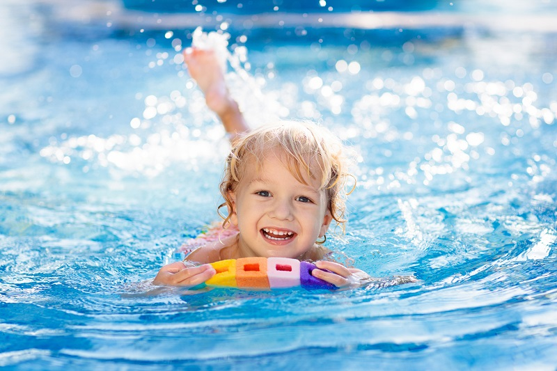 Three-year-old boy splashing in a swimming pool and using a colourful float board.