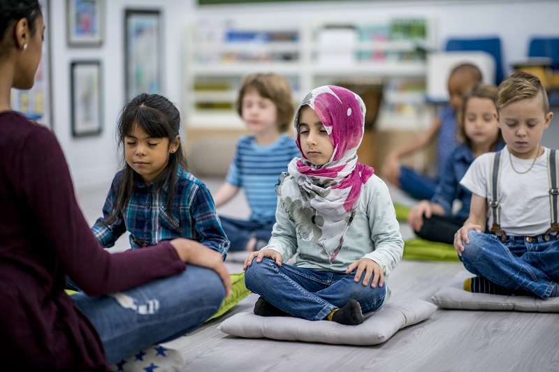 Young school children meditating on mats, being led by a teacher