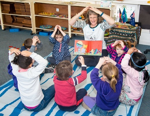 Group of children at preschool seated on mat being read a book by educator and doing actions to a song