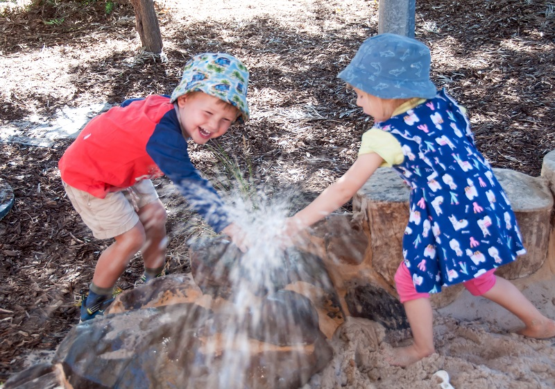 Preschool girl and boy having fun with water fountain at edge of sandpit