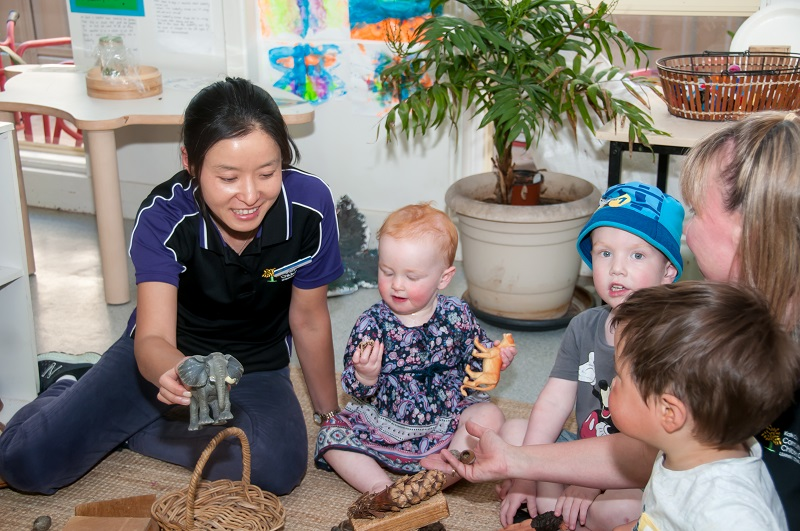 Two female educators playing with children on floor