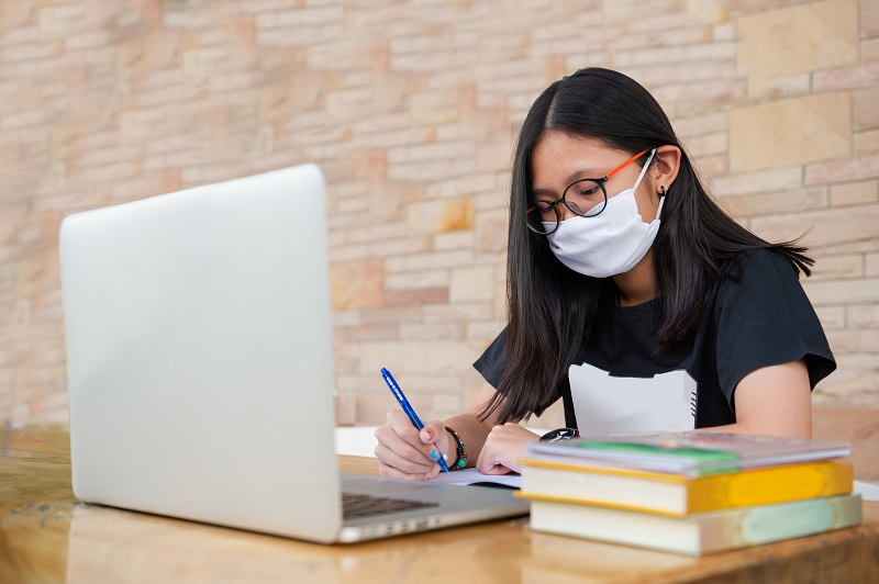 Female student studying at a table with her laptop and wearing a face mask