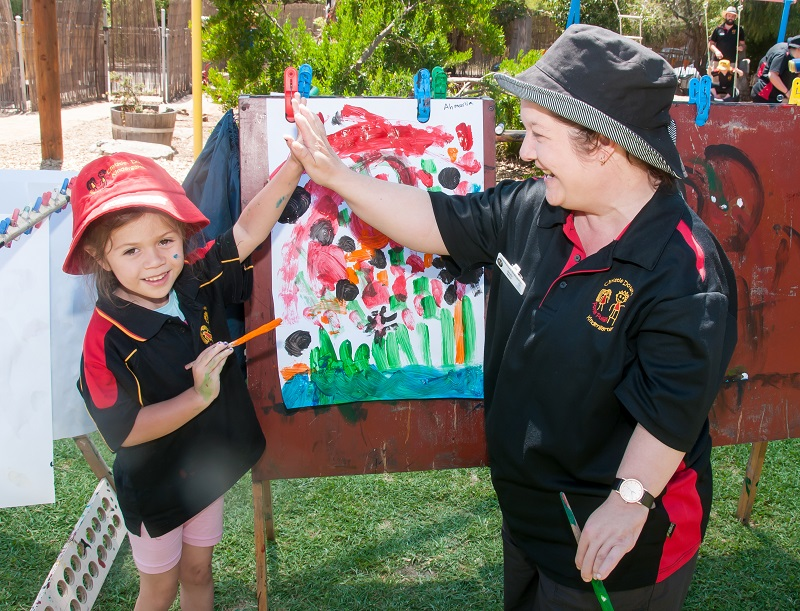 Kindergarten girl with colourful painting outside 'high-fiving' a smiling female educator.