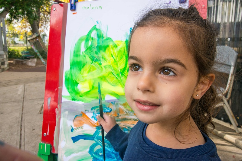 Preschool girl holding a paint brush with her painting on an easel behind her