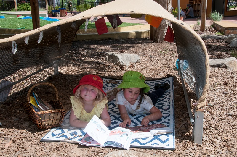 Two preschool girls wearing hats and reading on a mat under a shade hut.