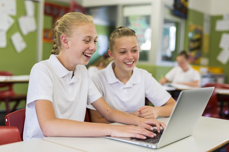 High school girls smiling while using a laptop together