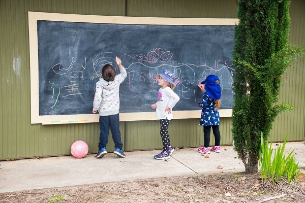 Photo of three children writing on blackboard outside at kindy