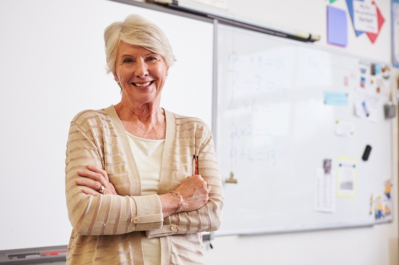 Female school principal with whiteboard in background