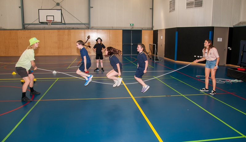 Three primary school girls skipping a large rope turned by educators in a gym