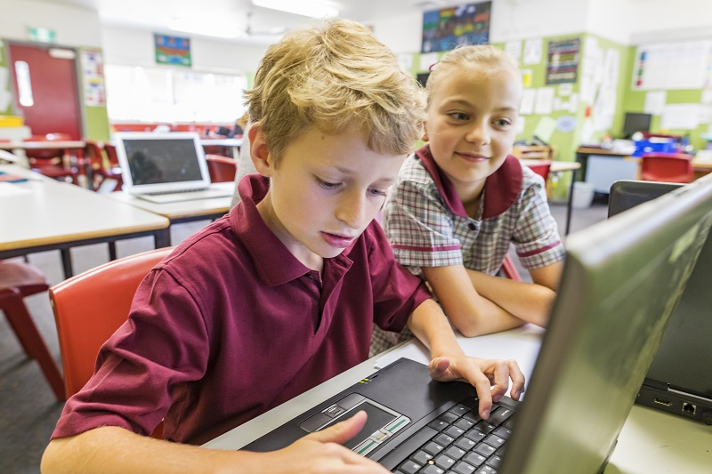 Primary school boy and girl in red school uniforms using computer at school
