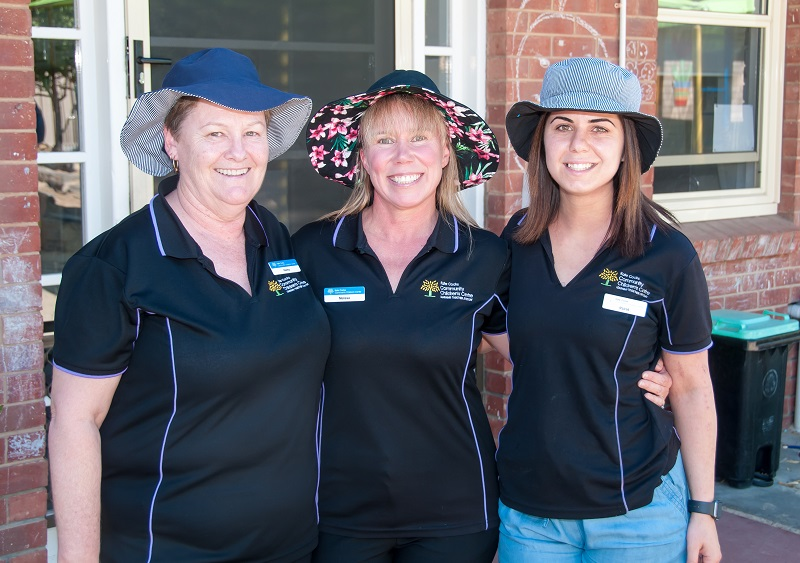 Three female early childhood workers wearing hats and smiling.
