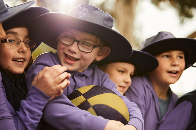 Primary school children in blue uniforms wearing broad-brimmed sun hats with a little sun glare visible