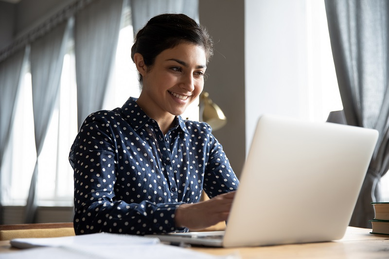 Woman sitting at laptop and smiling