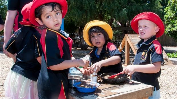 Children playing at a mud kitchen outdoors