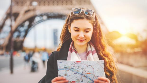 Female student with map near Eiffel Tower
