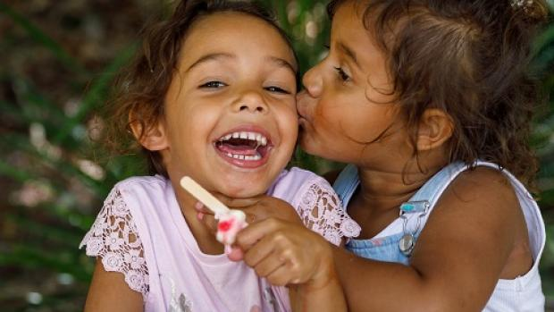 Two happy preschool Aboriginal girls: one eating an iceblock while being kissed on the cheek by the other