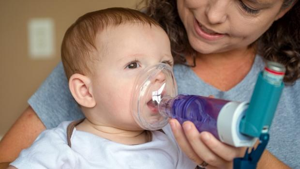 Baby being given asthma inhaler by a female carer, using a mask and spacer