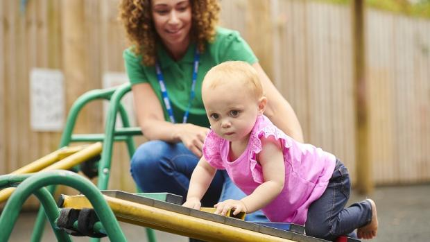 Baby crawling on play equipment with female educator supporting