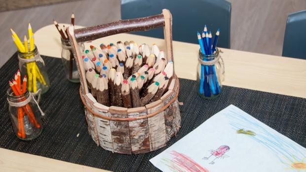 Big pot of thick, rustic wooden pencils on a low desk, along with a child's drawing and other smaller pencil pots