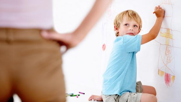 Preschool boy drawing on wall being discovered by an educator