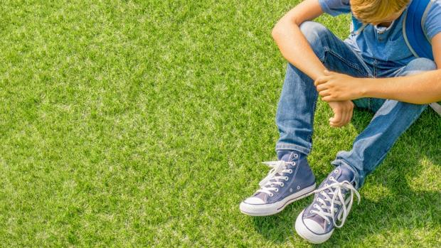 Boy of primary school age on grass looking downcast