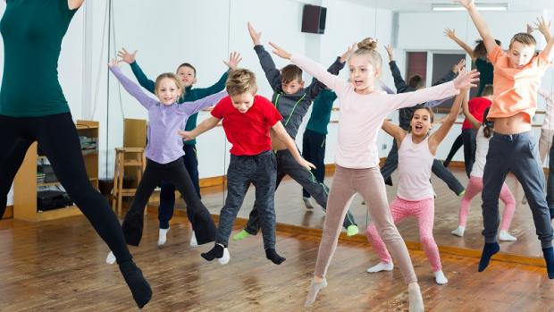 Primary school children doing a dance class led by a female teacher