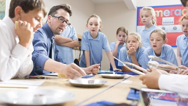Male teacher demonstrating something to primary school children in blue uniforms, many of whom are holding tongs