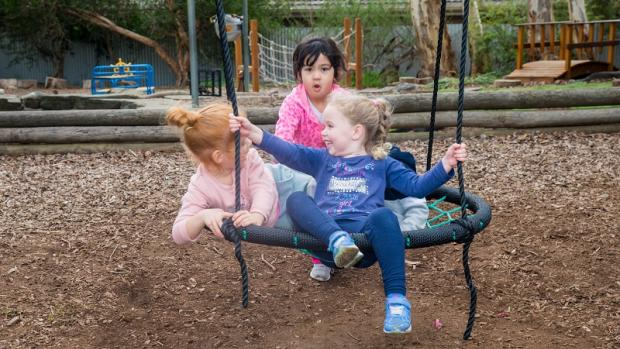 Three girls and a boy play on a big swing outside at a kindergarten with trees, logs and play equipment in the background
