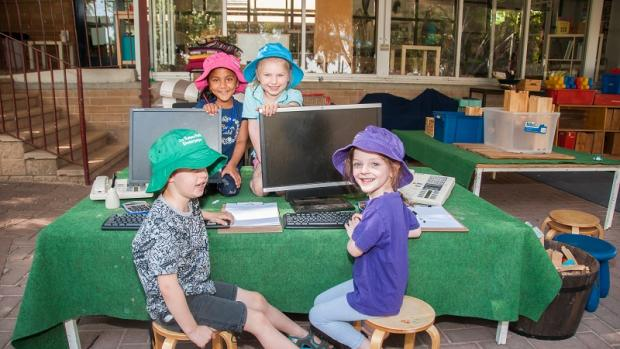 Four children playing with toy computers outside at preschool