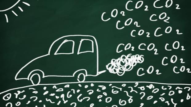 Child's chalk drawing on blackboard of car releasing C02 pollution from its tailpipe