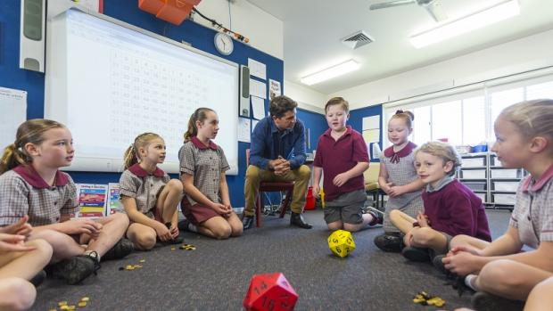 Primary school children in circle with teacher rolling big dice