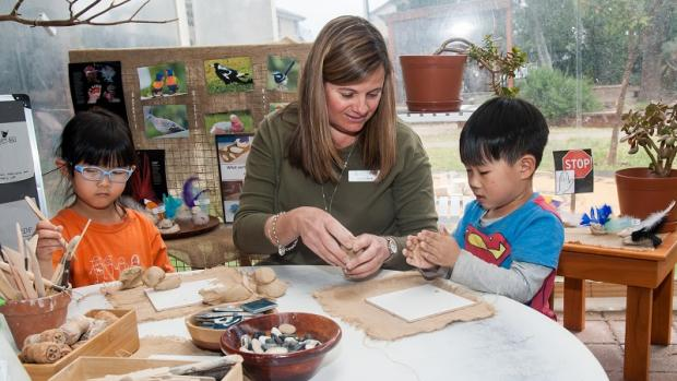 Kindergarten teacher showing two children how to model with clay