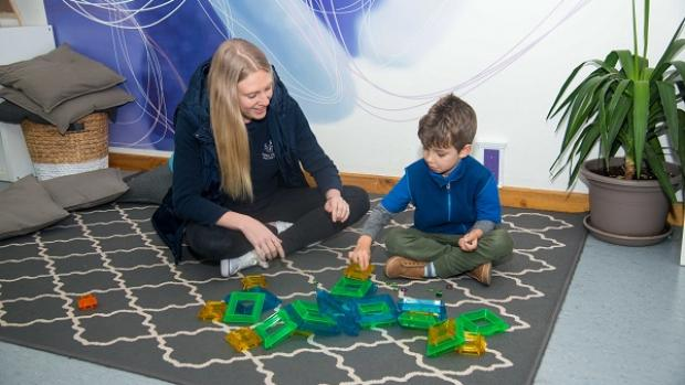 Photo of female educator playing with male child on floor