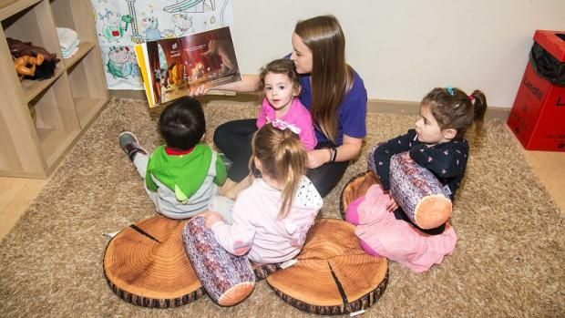 Educator reads a picture book to preschool children on floor mat