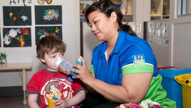 Female educator giving a boy an asthmas puffer at day care