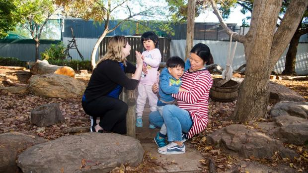 Educator helping a mum to drop off her children at an an education and care service