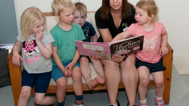 Female educator sitting on couch reading to several children sitting around her