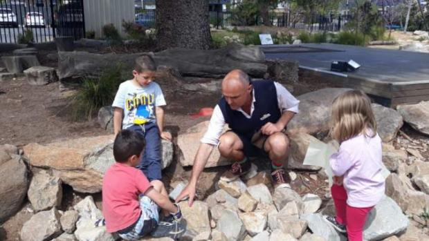 Children and teacher look for creatures among large rocks