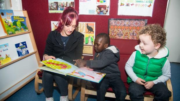 Young female educator reading to two preschool boys on couch