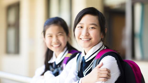 Two happy-looking high school girls of Asian appearance wearing school uniforms