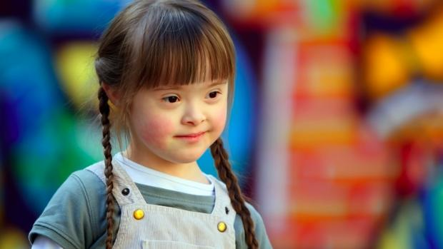 Preschool girl with Down syndrome against colourful background