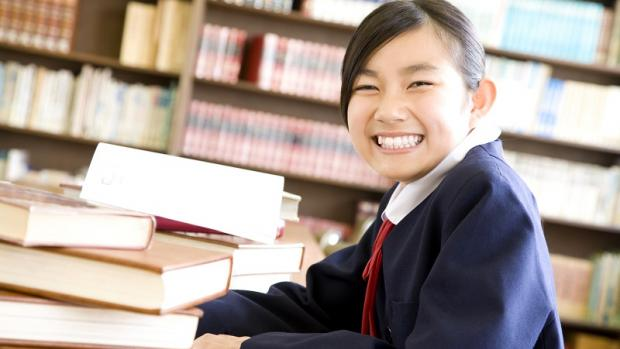 Female high school student wearing blue uniform in library smiling while surrounded by heavy books