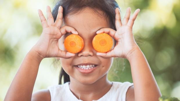 Girl putting carrot rounds on her eyes