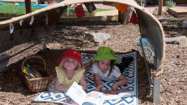 Two preschool girls wearing hats and reading on a mat outside under a shade hut