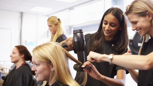 Female student assists with drying a client's hair in a hair salon