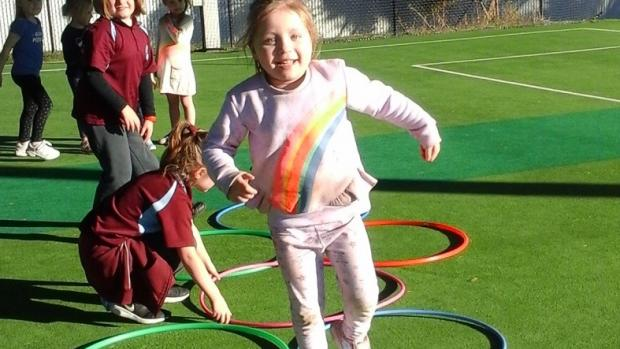 Primary-school-aged girl hopping through hoops on grassed tennis court with other children in background
