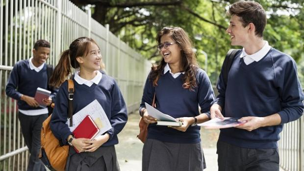 High school students in uniform: one boy of African background (in background), two girls of Asian background and one boy of Anglo background (in foreground)